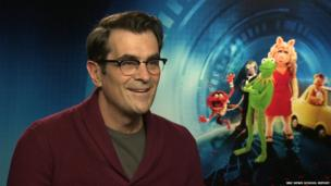 Ty Burrell in front of Muppets poster