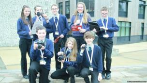 Students stand before the camera with their equipment and note pads