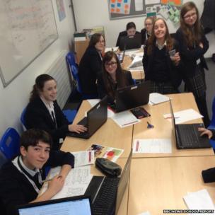 School Reporters pose at their desks whilst at work