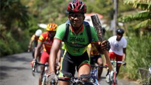 Cyclist Tessimy Viechweg rides with the Queen's baton in Grenada.