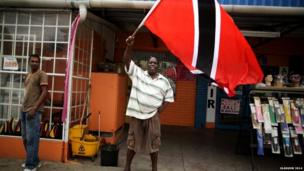 A man shows his patriotic support for the Queen's Baton Relay by waving a large national flag in Port of Spain, Trinidad.