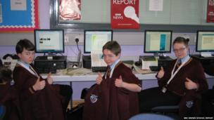 Three students from St. Pius X College put their thumbs up for the camera whilst sitting at their desks