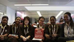 Students with a news school report cube