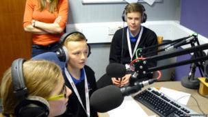 Llanishen High School sit in the recording studio with microphones and headphones