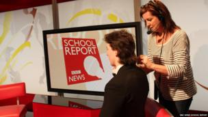 School reporter Connor getting mic'd up by floor manager Debby