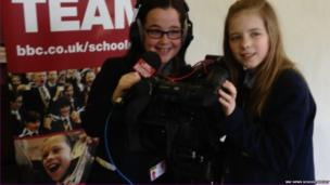 School Reporters holding a tv camera in front of a School Report banner