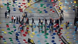 People cross stepping-stones underneath an artwork made of coloured umbrellas along the Cheonggye stream in central Seoul, South Korea