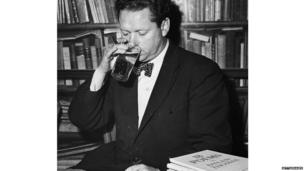 Welsh poet Dylan Thomas (1914 - 1953) drinking a glass of beer and smoking while seated at a desk with stacks of his books of poetry, New York City, c. 1950.