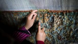 Kameleh, seven, weaves a carpet in a house used as a traditional carpet workshop in Herat, Afghanistan