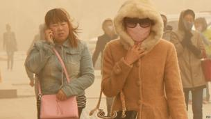 Residents walk through during a sandstorm in Hami, China