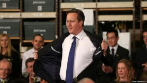 Prime Minister David Cameron takes his jacket off as he prepares to answer questions from staff at the John Lewis store, in Cheadle, Greater Manchester