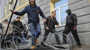 Pro-Russian protesters walk across barbed wire as they storm the regional government building in Donetsk on 6 April 2014.