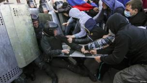 Pro-Russian protesters scuffle with the police near the regional government building in Donetsk on 6 April 2014.