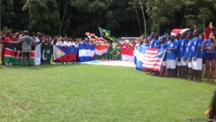 Children lining up behind national flags on a football pitch
