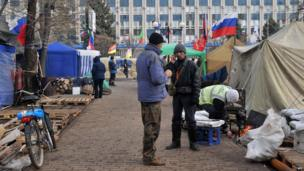 Two men talk, surrounded by tents and Russian flags, at the pro-Russia camp outside the Ukrainian security service building in Lugansk.