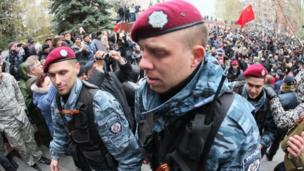 Members of the disbanded Berkut riot police force, together with pro-Russian separatists, enter the seized regional police headquarters in Donetsk. An old USSR flag flies in the distance.