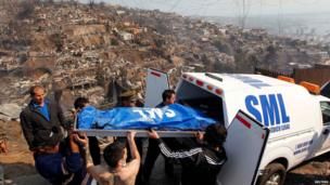 Residents and rescue workers remove a body in Valparaiso, April 13, 2014.