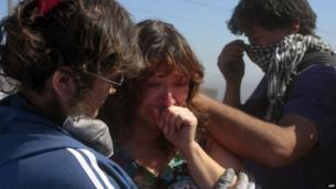 A woman is comforted by relatives after a huge fire devastated her home in Valparaiso, on April 14, 2014.