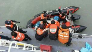 This South Korea Coast Guard handout photo taken at sea some 20km (12 miles) off the island of Byungpoong in Jindo on 16 April 2014 shows South Korea Coast Guard members rescuing some of the passengers and crew aboard a South Korean ferry sinking on its way to Jeju island from Incheon