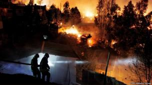 Firefighters work to put out a fire in Valparaiso city, northwest of Santiago