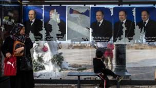 A woman stands at a bus stop beside election campaign posters in Algiers