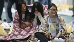 Traumatised passengers who were rescued sit inside a gym in Jindo - 16 April 2014