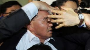 South Korean Prime Minister Chung Hong-won is shielded by his bodyguards from angry relatives of passengers from a ferry Sewol sinking in the water off the southern coast at a shelter for relatives of passengers in Jindo, south of Seoul, South Korea, on Thursday, 17 April, 2014