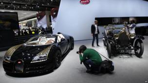 Visitors take photos of Bugatti cars on display at the Beijing Auto Show