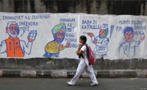 A school girl walks past a wall with graffiti depicting Indian politics in Calcutta.