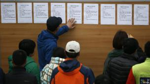 The families of missing passengers look at a noticeboard with descriptions of bodies - 22 April 2014