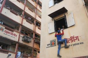 """Indian climber and independent political candidate, Gaurav Sharma, wearing a """"spiderman"""" costume, climbs to the window of a residential building and speak to residents as he campaigns for the Lok Sabha elections in Mumbai on April 11, 2014."""