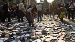 People collect free books offered by a publishing house on International Book Day in Bucharest, Romania