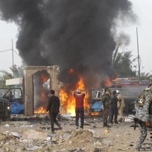 Iraqi security forces react at the scene of a car bomb attack in Baghdad on 25 April 2014.