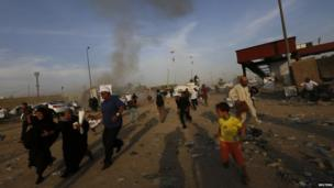 People react after a car bomb attack at a Shia political organisation's rally in Baghdad on 25 April 2014.