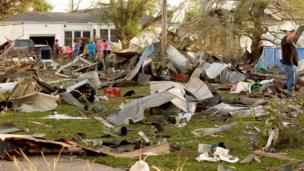Residents survey the damage in a residential neighbourhood in Quapaw struck by a tornado on 27 April