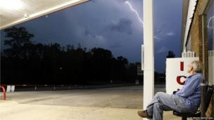 Jimmy Sullinger, sits and watches lightning as a storm approaches the gas station where he works on 28 April in Berry, Alabama.