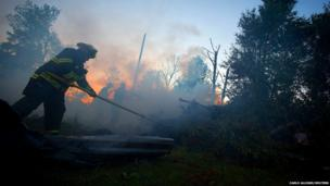 Firefighters knock down a small brush fire after sunset in Vilonia, Arkansas