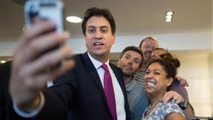 Britain's Labour Party leader Ed Miliband takes a picture in a hairdressers in Cambridge city