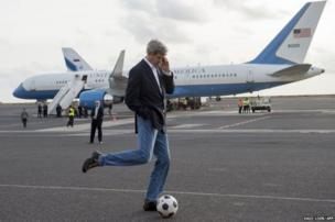 US Secretary of State John Kerry kicks a football during an aeroplane refuelling stop at Sal Island, Cape Verde