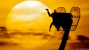 People in a fairground ride are silhouetted against the setting sun