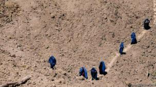 Afghan women arrive at the site of a landslide, after the dead body of a woman was found, at the Argo district in Badakhshan province