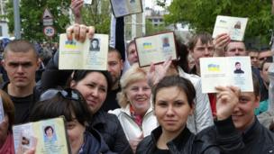 Ukrainians, who are in Russia at the moment, show off their passports while queuing to get their referendum ballot papers and vote, in Moscow, Russia, on Sunday, May 11, 2014.