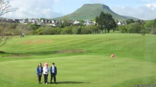 Two School Reporters and woman in pink wig on a golf course, large hill in background