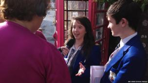 Woman and two School Reporters being interviewed in front of a red telephone box