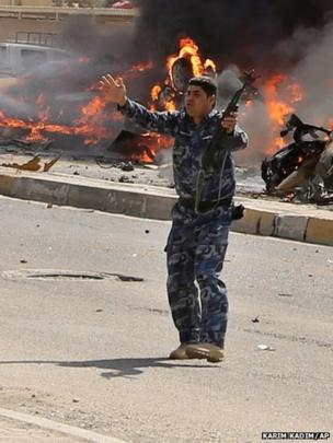 An Iraqi policeman gestures near burning vehicles moments after one in a series of bombs hit Sadr City