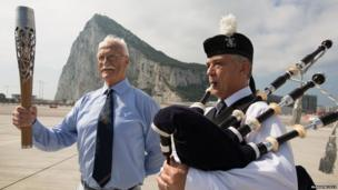 An elderly gentleman holds the Queen's Baton next to a man playing bagpipes. The Rock of Gibraltar is in the background.