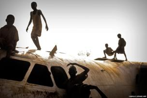 Young refugees play on an aircraft that crashed in November 2012 on the Yida airstrip, South Sudan
