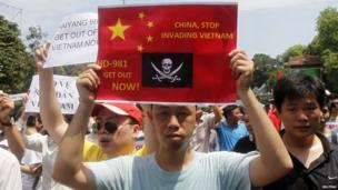 Protesters hold anti-China placards while marching in an anti-China protest on a street in Hanoi on 11 May, 2014