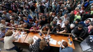 People stand in a line to receive ballots from members (front) of a local election commission during the referendum on the status of Donetsk