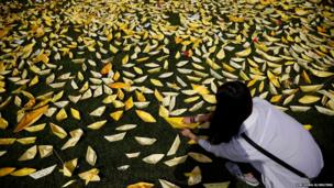 A woman places a yellow-coloured paper ship dedicated to dead and missing passengers onboard sunken passenger ship Sewol at Seoul City Hall Plaza